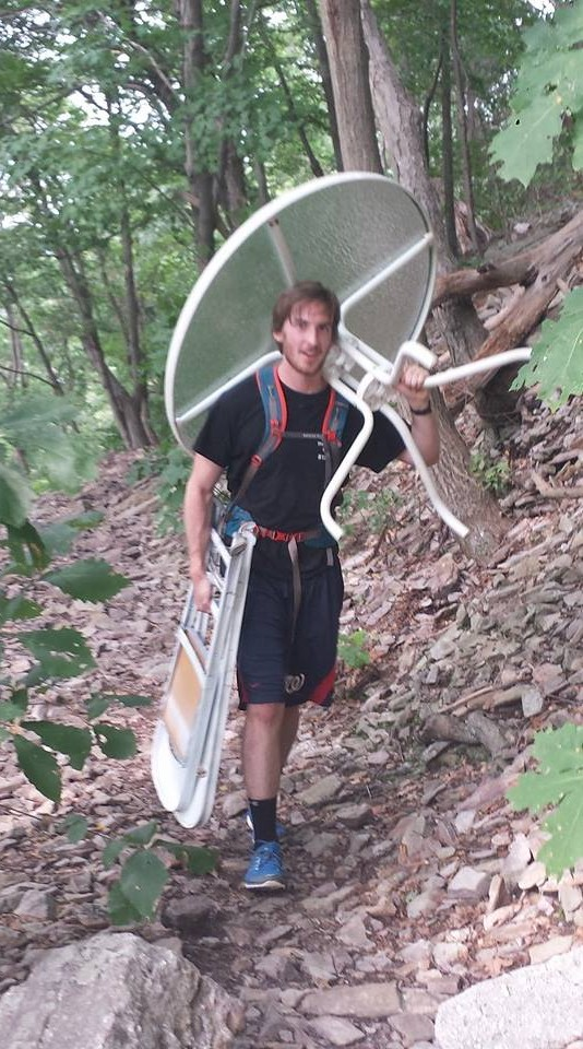 Hiker carrying patio furniture up to Hawk Rock